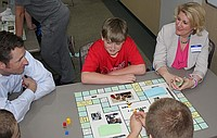 "Parents and their children play a board game during one of the Lawrence-Douglas County Health Department's ""Kids Need To Know"" classes. The Health Department is accepting enrollment for a fall co-ed class that begins Oct. 11."