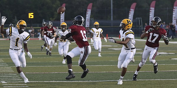 Lawrence High School receiver Ekow Boye-Doe (12) catches a pass in the 1st quarter to set up a Lions touchdown in their win against Shawnee Mission West Friday night at LHS.