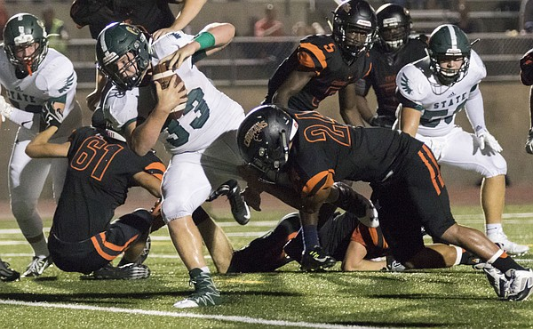Free State High sophomore Jax Dineen (33) pulls Shawnee Mission Northwest senior Xavier Perry (24) into the end zone with him during their game Friday night in Shawnee.
