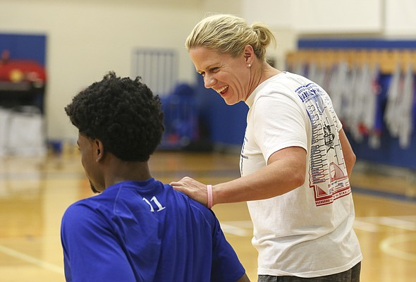 Trainer Andrea Hudy jokes with freshman Josh Jackson as the players get stretched out prior to the start of Boot Camp in the practice gym on Friday, Sept. 23, 2016 just after 6 a.m.