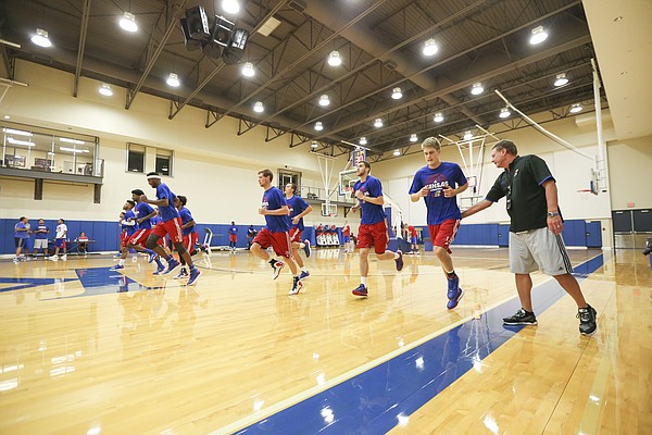 Kansas head coach Bill Self gives some encouragement to newcomer Tucker Vang during Boot Camp in the practice gym on Friday, Sept. 23, 2016 just after 6 a.m.