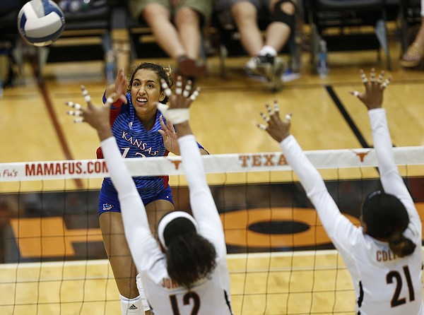 Kansas' Patricia Montero (13) hits a kill past Texas' Morgan Johnson (12) and Chloe Collins (21) during a match at Gregory Gym in Austin, Saturday, Sept. 24, 2016.