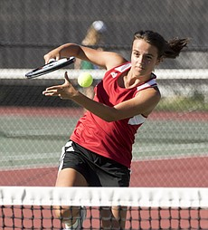 Lawrence High's Natalie Cote hits a volley at the net during her number one doubles match against Free State High on Tuesday afternoon at LHS.