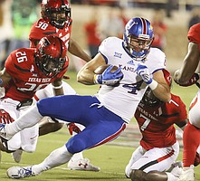 Kansas tight end Ben Johnson (84) is brought down after a catch during the first quarter on Thursday, Sept. 29, 2016 at Jones AT&T Stadium in Lubbock, Texas.