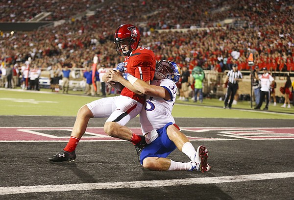 Kansas special teams player Keith Loneker (33) pulls down Texas Tech place kicker Erik Baughman (36) for a safety during the second quarter on Thursday, Sept. 29, 2016 at Jones AT&T Stadium in Lubbock, Texas.