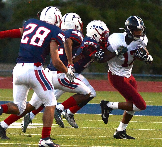 Clarence King (17) tries to elude a triple threat of Eagles as Lawrence played Olathe North on Friday night at ODAC.