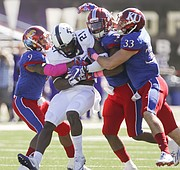 Kansas defenders Fish Smithson, (9), Greg Allen and Keith Loneker Jr. (33) bring down TCU running back Kyle Hicks (21) during the fourth quarter on Saturday, Oct. 8, 2016 at Memorial Stadium.