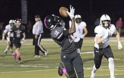 After getting behind the Shawnee Mission East secondary, Lawrence High junior receiver Ekow Boye-Doe (12) hauls in a long pass for a touchdown during their game Friday night at LHS.