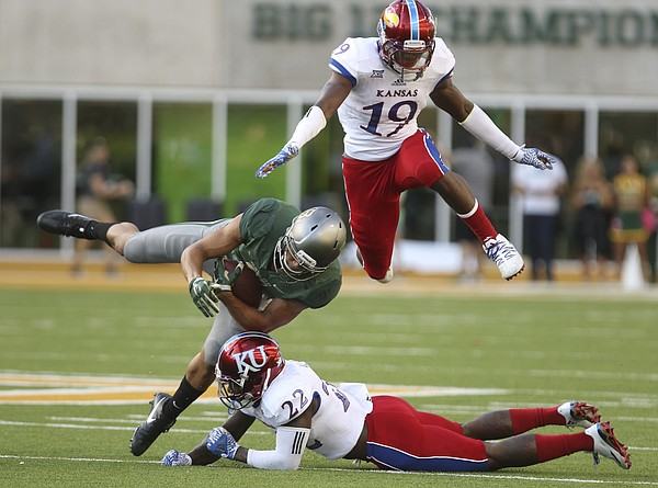 Kansas defensive end Isaiah Bean (19) gets airborne as he and safety Greg Allen (22) take out Baylor wide receiver Blake Lynch (2) during the fourth quarter on Saturday, Oct. 15, 2016 at McLane Stadium in Waco, Texas.