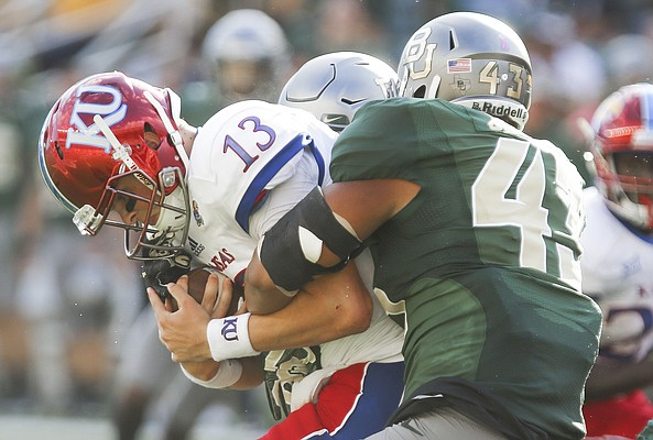 Kansas quarterback Ryan Willis (13) is sacked by Baylor defensive end Jamie Jacobs (43) during the third quarter on Saturday, Oct. 15, 2016 at McLane Stadium in Waco, Texas.