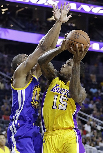 Los Angeles Lakers' Thomas Robinson shoots against Golden State Warriors' James Michael McAdoo during the second half of an NBA preseason basketball game Saturday, Oct. 15, 2016, in Las Vegas. (AP Photo/John Locher)