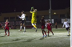 Lawrence High senior DJ Davis (#20) directs a header on net into the arms of Shawnee Heights goalie Tyler Zentner (#1) during the first of the LHS boys soccer team's Senior Night on Thursday, Oct. 20, 2016.