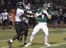 Free State High senior Daniel Bryant (4) hauls in a pass after getting behind Lawrence High defenders James Reeder (20) and Cade Burghart during their game Friday night at FSHS.