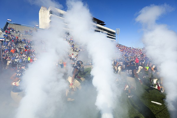 Kansas offensive lineman Antione Frazier (75) and the Jayhawks head out to the field through the smoke prior to kickoff on Saturday, Oct. 22, 2016 at Memorial Stadium.