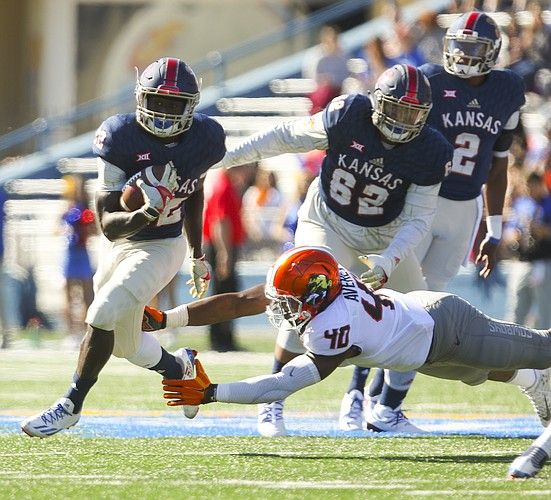 Kansas running back Ke'aun Kinner (22) evades Oklahoma State linebacker Devante Averette (40) during the first quarter on Saturday, Oct. 22, 2016 at Memorial Stadium.