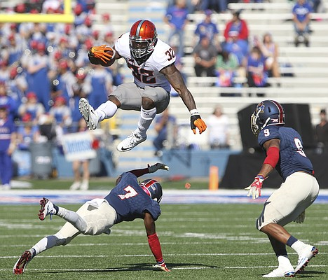 Oklahoma State running back Chris Carson (32) hurdles Kansas cornerback Derrick Neal (7) after a catch during the fourth quarter on Saturday, Oct. 22, 2016 at Memorial Stadium. Kansas safety Fish Smithson (9) is at right.