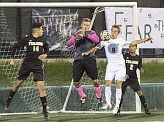 Free State High junior Nicholas Howard (8) tries to score in front of the goal as Topeka's Brandon Wurtz (14), goalkeeper Matthew Mahn, center, and Guillermo Gutierrez (2) provide defense during their first round regional soccer match Monday evening at FSHS.