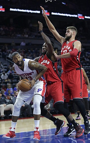 Detroit Pistons' Marcus Morris (13) tries to go to the basket against Toronto Raptors' DeMarre Carroll, center, and Jonas Valanciunas during the first half of an NBA preseason basketball game Wednesday, Oct. 19, 2016, in Auburn Hills, Mich. (AP Photo/Duane Burleson)