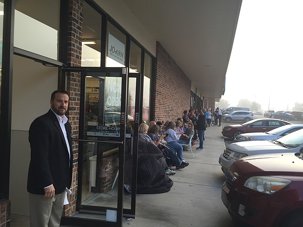 A crowd of people line up outside of Jo-Ann Fabric and Craft Store prior to its grand opening at 2108 W. 27th Street.