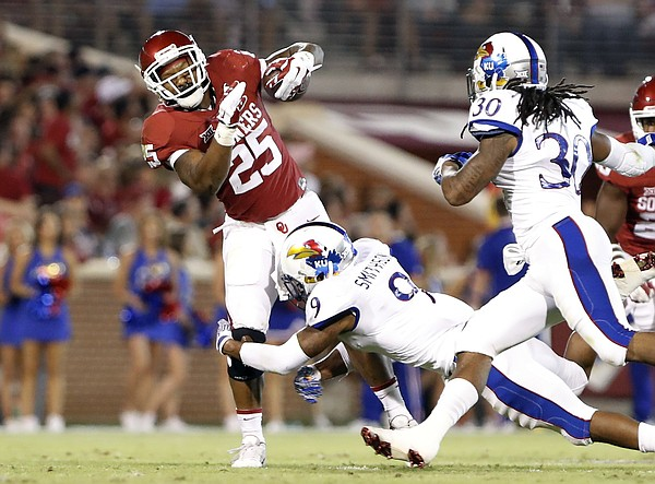 Oklahoma running back Joe Mixon (25) is tackled by Kansas safety Fish Smithson (9) during the first half of an NCAA college football game in Norman, Okla., Saturday, Oct.29, 2016.