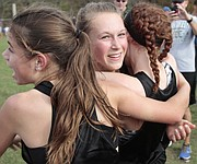 Free State senior Emily Venters (middle) hugs sophomores Julia Larkin (left) and Emma Hertig (right) seconds after finding out that the Firebirds won the Class 6A girls country championship Saturday at Rim Rock Farm. Venters was the 6A girls runner-up for the second straight year.