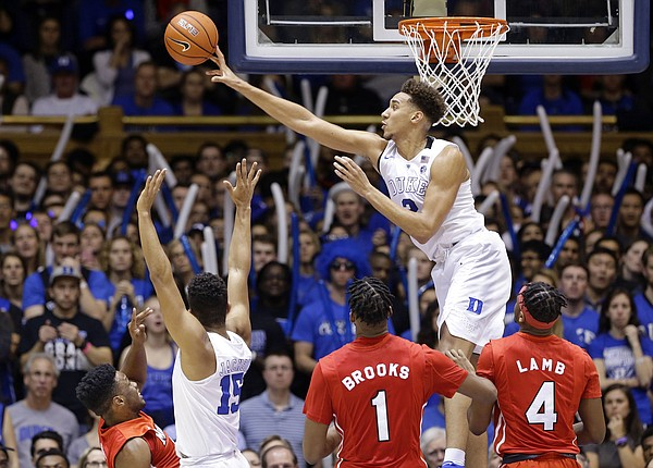 Duke forward Chase Jeter (2) blocks a shot by Marist guard Brian Parker, lower left, as Marist center Kentrall Brooks (1) and forward Isaiah Lamb (4) watch during the first half of an NCAA college basketball game in Durham, N.C., Friday, Nov. 11, 2016.