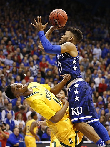 Siena guard Kadeem Smithen (14) falls backward as Kansas guard Frank Mason III (0) is whistled for a charge during the first half, Friday, Nov. 18, 2016 at Allen Fieldhouse.