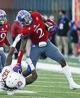 Kansas defensive end Dorance Armstrong Jr. (2) puts Texas running back D'Onta Foreman (33) on the ground after recovering a fumble during the second quarter on Saturday, Nov. 19, 2016 at Memorial Stadium.