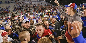 Kansas place kicker Matthew Wyman (7), center, is mobbed by KU students and fans after his game-winning field goal during overtime against Texas on Saturday, Nov. 19, 2016 at Memorial Stadium.