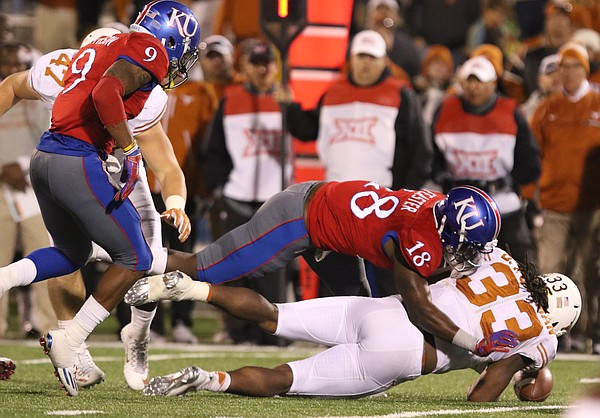 Kansas linebacker Denzel Feaster (18) knocks the ball loose from Texas running back D'Onta Foreman (33) during the fourth quarter to give the ball back to the Jayhawks with little time remaining on Saturday, Nov. 19, 2016 at Memorial Stadium.