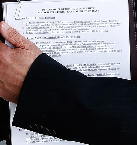 Kansas Secretary of State Kris Kobach holds a packet of papers while posing with Donald Trump in this cropped and rotated photo from the Trump National Golf Club Bedminster clubhouse, Sunday, Nov. 20, 2016, in Bedminster, N.J.. (AP Photo/Carolyn Kaster)