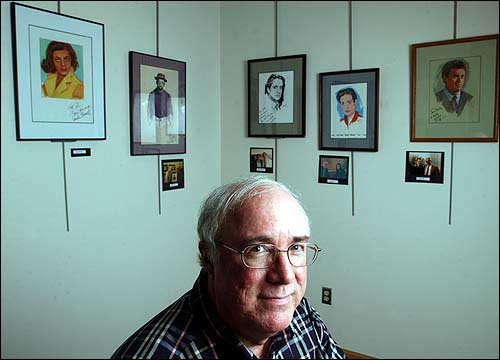 John Tibbetts is pictured, along with some of the celebrity portraits he's painted and had autographed, in this 2004 Journal-World file photo. Tibbetts is an associate professor of film and media studies at the University of Kansas.