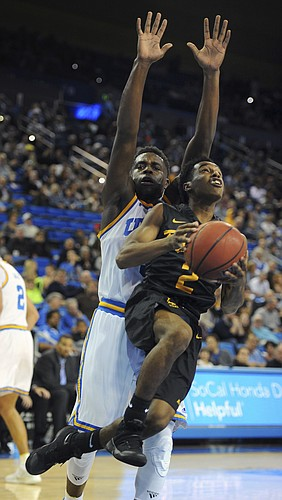 Long Beach State's Loren Jackson goes for a layup around UCLA's Aaron Holiday during the second half of an NCAA college basketball game in Los Angeles, Sunday, Nov. 20, 2016. UCLA beat Long Beach State 114-77.