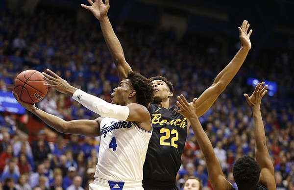 Kansas guard Devonte' Graham (4) gets in for a bucket past Long Beach State forward LaRond Williams (22) during the first half, Tuesday, Nov. 29, 2016 at Allen Fieldhouse.