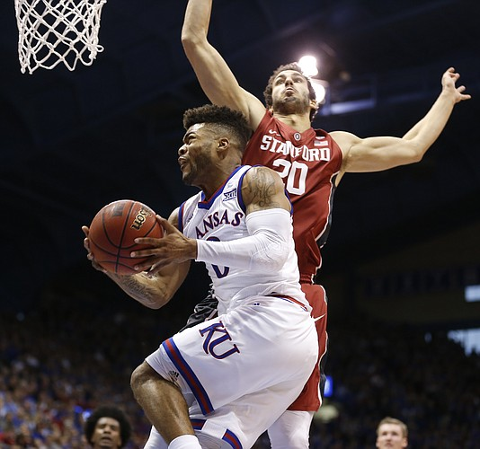 Kansas guard Frank Mason III (0) gets under Stanford center Josh Sharma (20) for a reverse layup and a foul during the second half on Saturday, Dec. 3, 2016 at Allen Fieldhouse.