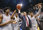 Kansas head coach Bill Self raises up a ceremonial ball commemorating his 600th win as he celebrates with his players and those attending the Jayhawks