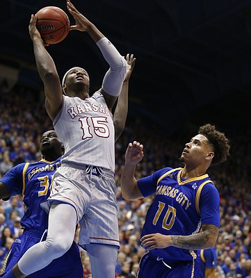 Kansas forward Carlton Bragg Jr. (15) gets in for a bucket over UMKC forward Aleer Leek (30) and UMKC guard Broderick Robinson (10) during the second half, Tuesday, Dec. 6, 2016 at Allen Fieldhouse.