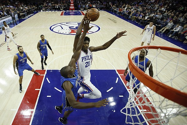 Philadelphia 76ers' Joel Embiid (21) goes up for a dunk against Orlando Magic's Bismack Biyombo (11) during the first half of an NBA basketball game, Friday, Dec. 2, 2016, in Philadelphia. (AP Photo/Matt Slocum)