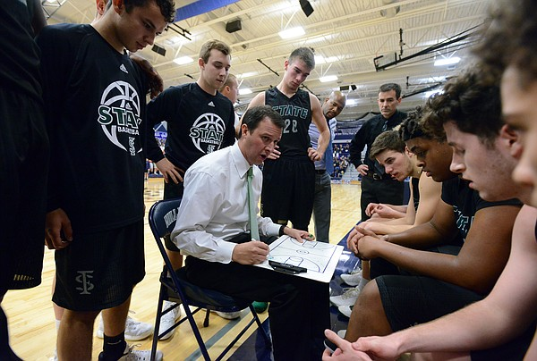 During a timeout, head coach Sam Stroh talks with his team as Free State's boys basketball team played Mill Valley Friday in Shawnee.