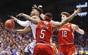 Kansas guard Frank Mason III gets an acrobatic shot to drop after a foul by Nebraska guard Glynn Watson Jr. (5) during the second half, Saturday, Dec. 10, 2016 at Allen Fieldhouse. At right is Nebraska forward Michael Jacobson (12).