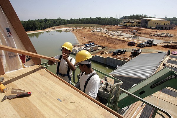 Workers install siding on the overlook at the U.S. National Whitewater Center in Charlotte, N.C., Tuesday, June 20, 2006. (AP Photo/Chuck Burton)