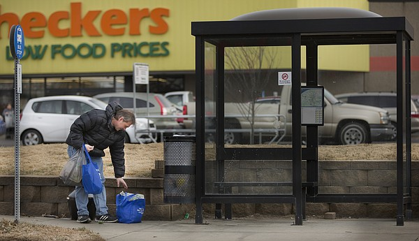 Lawrence resident Lance Fahy gathers his groceries as he waits for the bus to transport him home from Checkers on Thursday, Dec. 15, 2016. Fahy, who is visually impaired, is unable to drive and lives in the Pinckney neighborhood, which is within one of Lawrence's designated food deserts.