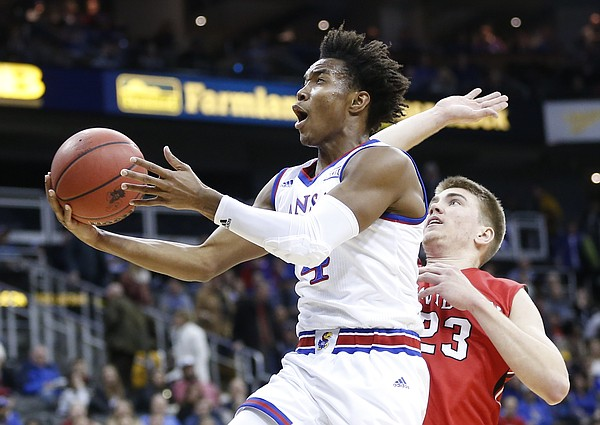Kansas guard Devonte' Graham (4) gets in for a bucket past Davidson forward Peyton Aldridge (23) during the first half, Saturday, Dec. 17, 2016 at Sprint Center.