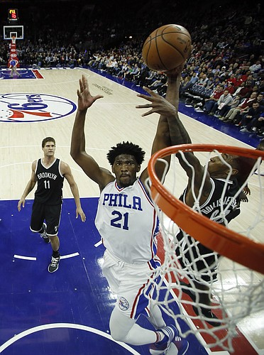 Philadelphia 76ers' Joel Embiid, center, goes up for a dunk against Brooklyn Nets' Rondae Hollis-Jefferson during the second half of an NBA basketball game, Sunday, Dec. 18, 2016, in Philadelphia. Philadelphia won 108-107. (AP Photo/Matt Slocum)