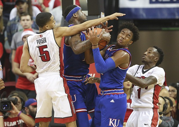 Kansas guard Devonte' Graham, right, and forward Carlton Bragg Jr. fight for a rebound with UNLV guards Jalen Poyser (5) and Kris Clyburn (1) during the second half, Thursday, Dec. 22, 2016 at Thomas & Mack Center in Las Vegas.