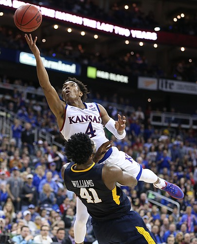 Kansas guard Devonte' Graham (4) is fouled by West Virginia forward Devin Williams (41) on the shot during the second half, Saturday, March 12, 2016 at Sprint Center in Kansas City, Mo.