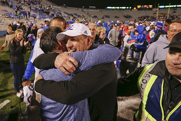 Kansas head coach David Beaty gets a hug from Kansas volleyball head coach Ray Bechard following the Jayhawks' 24-21 overtime upset of Texas on Saturday, Nov. 19, 2016 at Memorial Stadium. Saturday's victory was Beaty's first Big 12 coaching win. Bechard's volleyball team clinched a share of the Big 12 conference title with a win against Iowa State earlier in the day.