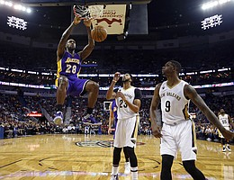 Los Angeles Lakers center Tarik Black (28) slam dunks over New Orleans Pelicans forward Anthony Davis (23) and forward Terrence Jones (9) in the second half of an NBA basketball game in New Orleans, Saturday, Nov. 12, 2016. The Lakers won 126-99. (AP Photo/Gerald Herbert)