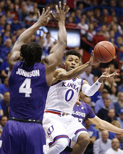 Kansas guard Frank Mason III (0) throws a pass around Kansas State forward D.J. Johnson (4) during the first half, Tuesday, Jan. 3, 2017 at Allen Fieldhouse.