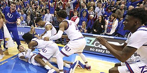 The Jayhawks file in to dogpile Kansas guard Sviatoslav Mykhailiuk (10) following Mykhailiuk's game-winning bucket to finish the game 90-88 against Kansas State on Tuesday, Jan. 3, 2017 at Allen Fieldhouse.